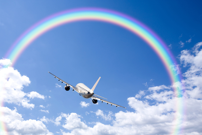 A jetliner aeroplane flying over white clouds towards a rainbow in blue sky